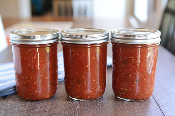 3 jars of homemade salsa lined up in a row on a wooden table.