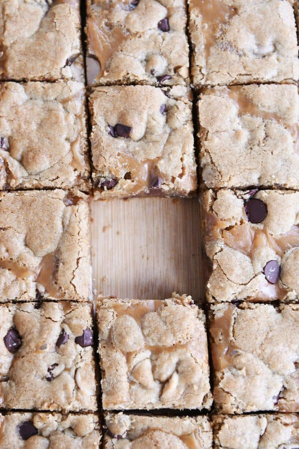 Slab of salted caramel brown butter chocolate chip bars cut into squares on wood cutting board.