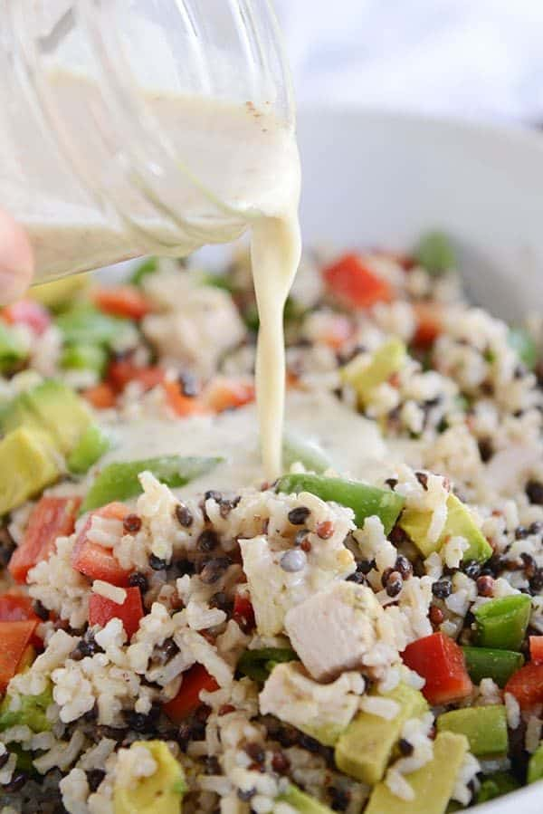 Dressing getting poured over a bowl of santa rosa chicken and wild rice salad.