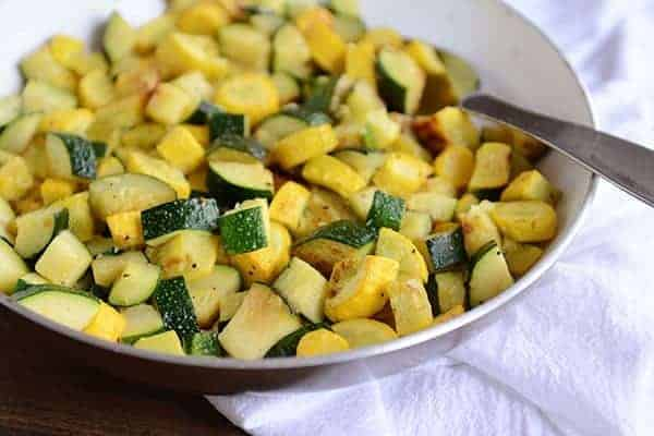 A skillet full of sautéed zucchini and yellow squash, with a full spoonful of the saute on top of the mixture.