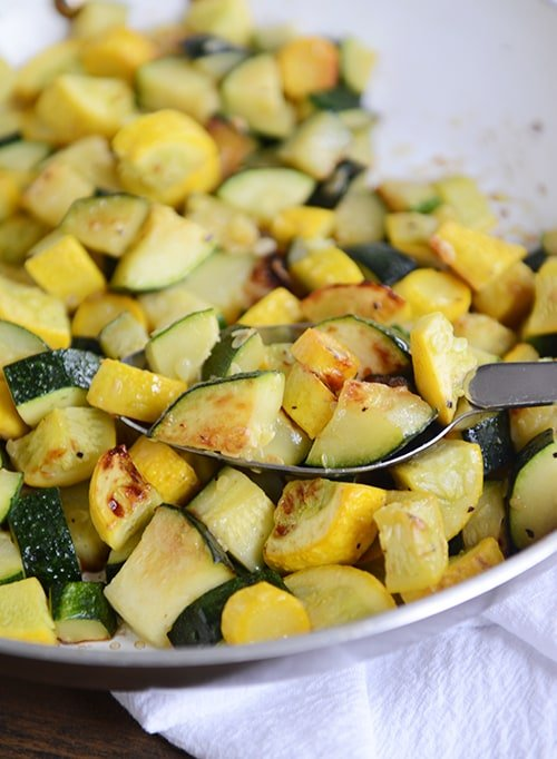 A plate full of sautéed zucchini and yellow squash, with a full spoonful of the saute on top of the mixture.