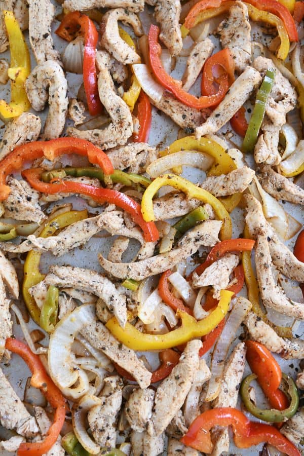 Sheet pan loaded with bell peppers and chicken strips for easy sheet pan chicken fajitas.