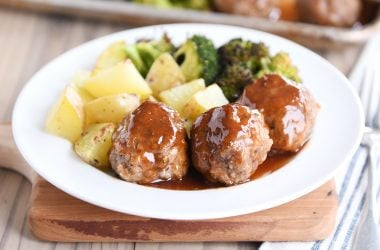 White plate filled with meatballs drizzled in sweet and sour sauce and roasted vegetables.