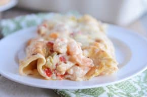 Closeup of two shrimp enchiladas on white plate.