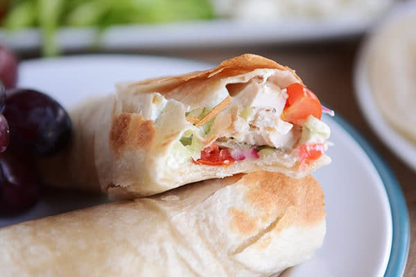 A greek chicken burrito split in half on a white plate.