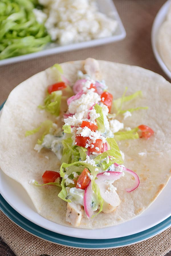 A tortilla filled with chicken, lettuce, onion, tomato, and feta.