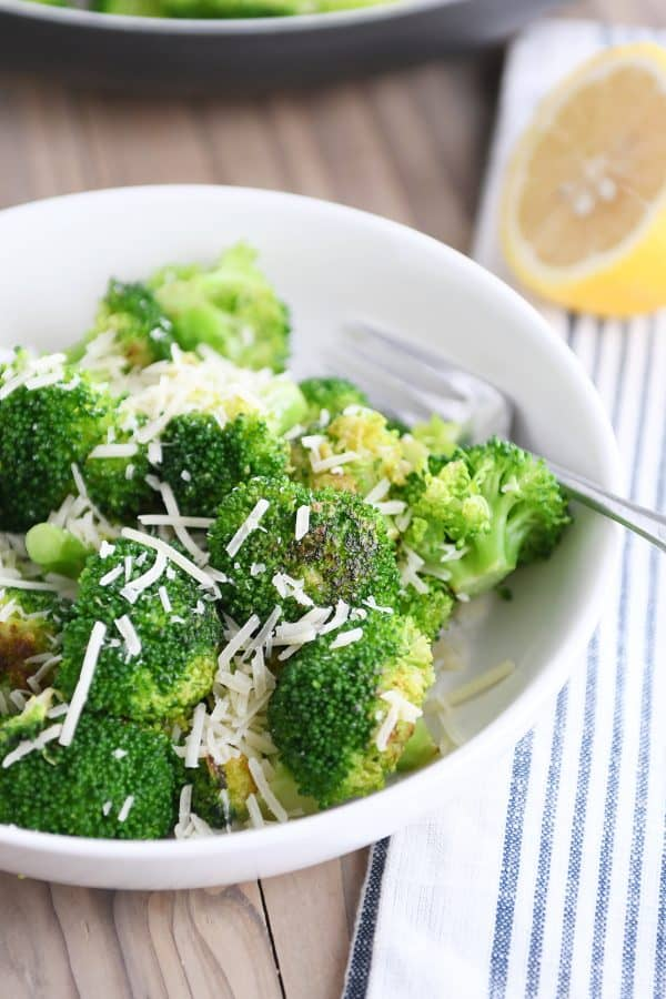 White bowl with skillet broccoli and Parmesan.