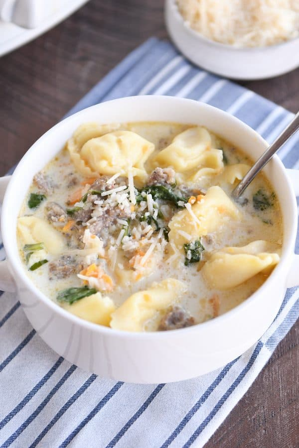 Spoon in white bowl with slow cooker tortellini sausage spinach soup.