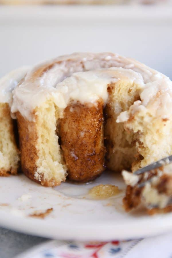 Half eaten cinnamon roll from small batch cinnamon roll recipe.