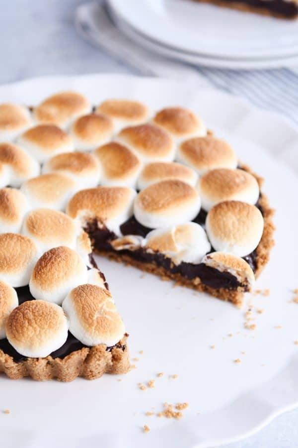 Slice taken out of full s'mores pie on white platter.