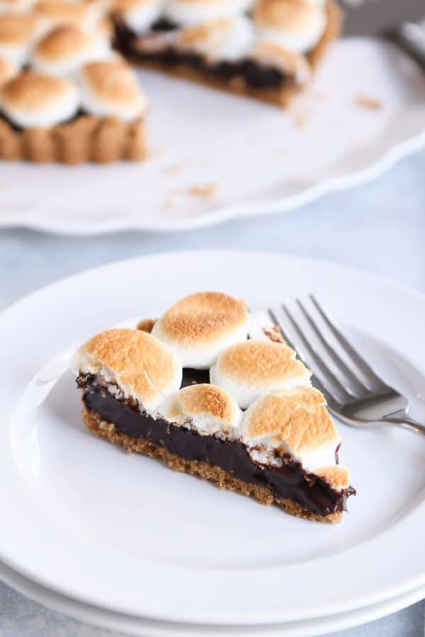 Piece of s'mores pie on white plate with fork.