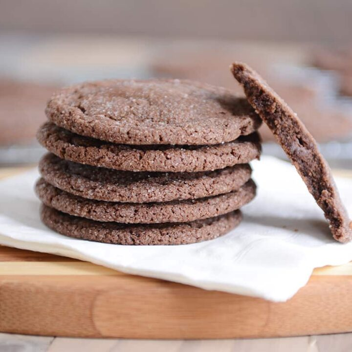 Stack of chocolate sugar cookies on a white napkin with one in half.