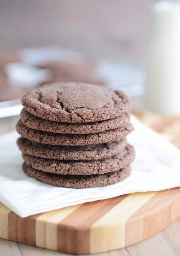 Stack of chocolate sugar cookies on white napkin.