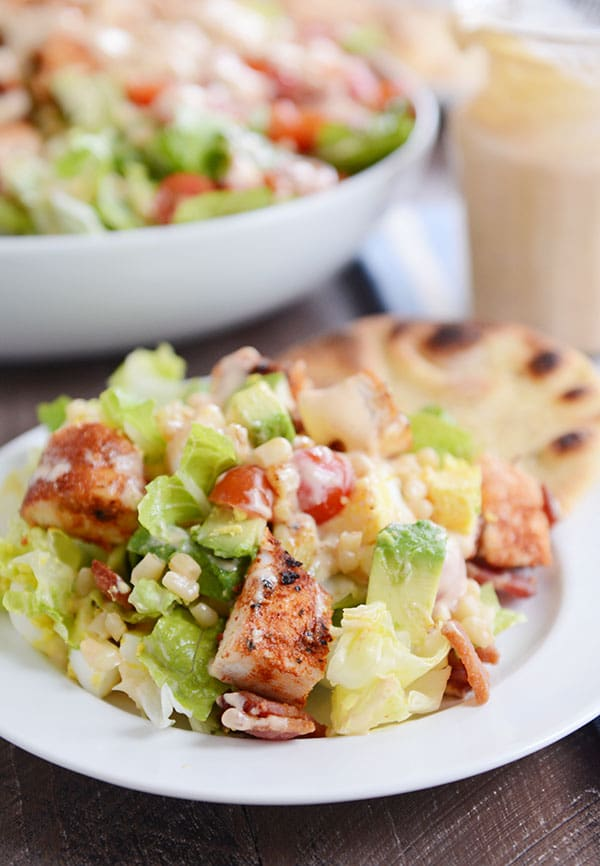 A grilled chicken cobb salad next to a flatbread on a white plate.