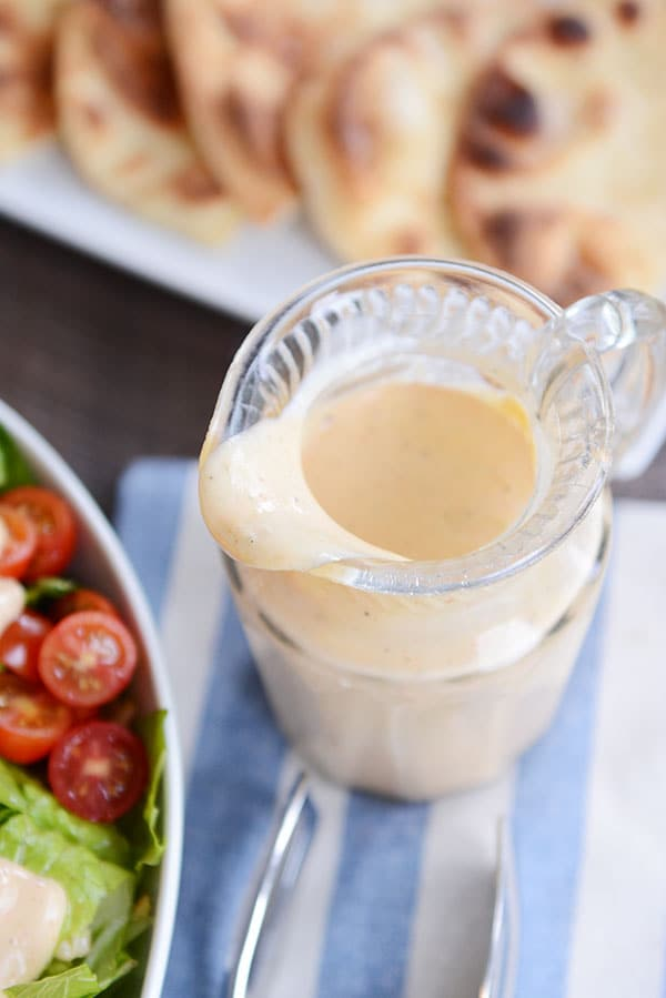 Top view of a glass pitcher of honey mustard dressing next to a plate of flatbread.