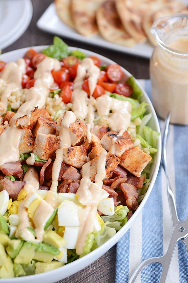 A white oval bowl full of grilled chicken cobb salad drizzled with a honey mustard dressing.