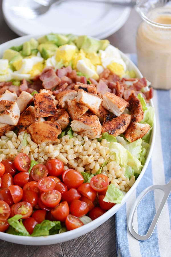 A large oval white bowl filled with tomatoes, rice, grilled chicken pieces, diced boiled egg, and diced avocado.