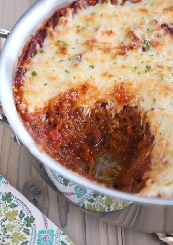 Spaghetti squash spaghetti bake topped with cheese in pan.