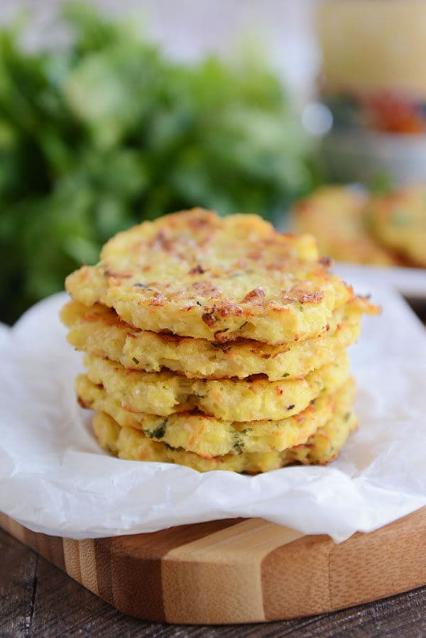 Five golden brown spaghetti squash fritters on a piece of parchment paper.