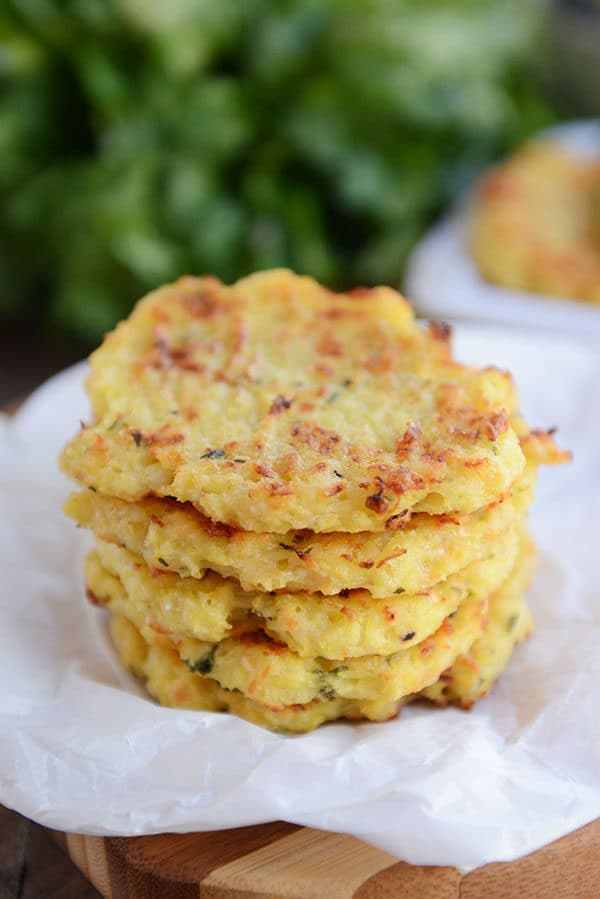 A stack of golden brown spaghetti squash fritters on a piece of parchment.