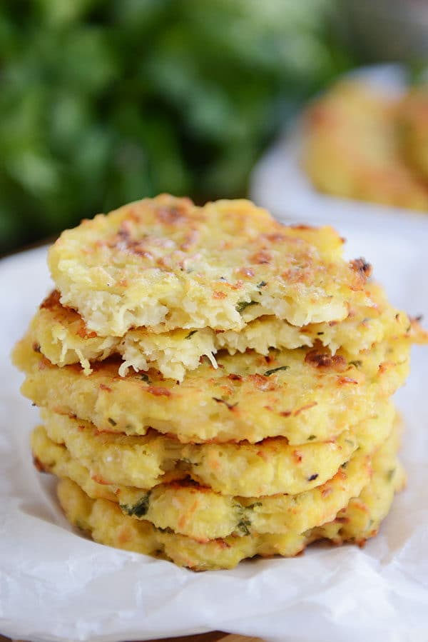 A stack of spaghetti squash parmesan fritters with the top one split in half on a piece of parchment.