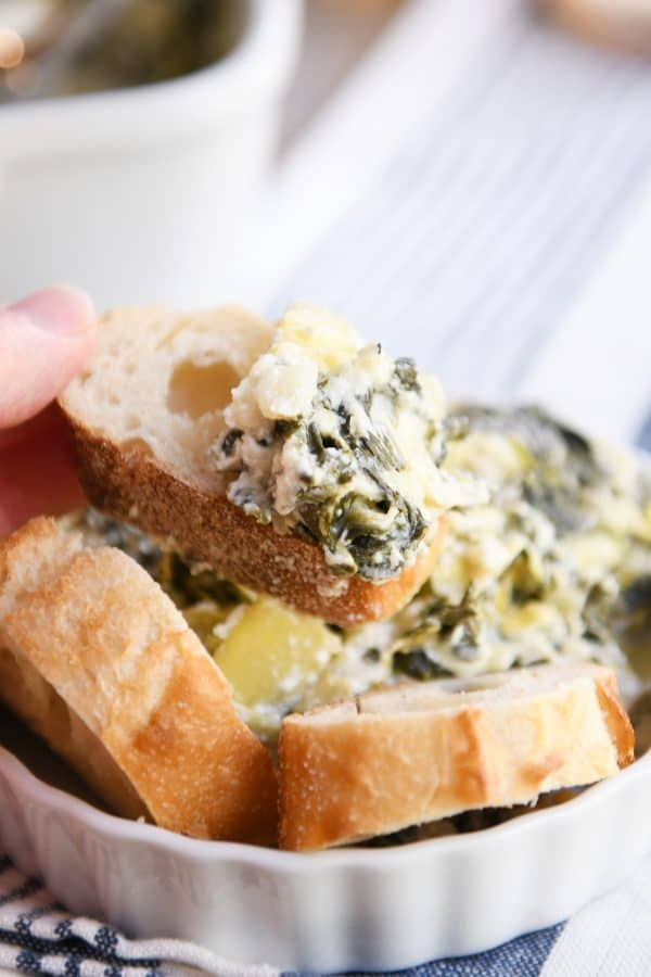 The best spinach artichoke dip in white dish with bread.