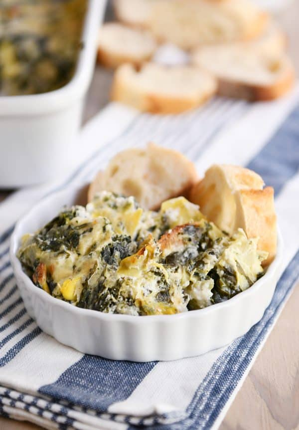 The best spinach artichoke dip in white dish with bread slices.