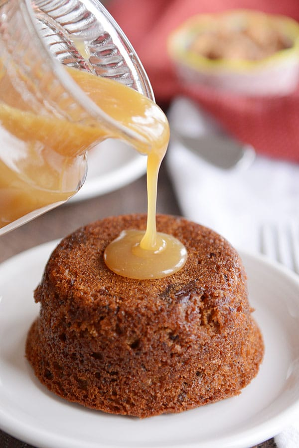 A small, brown cake on a white plate, with light brown sticky toffee sauce