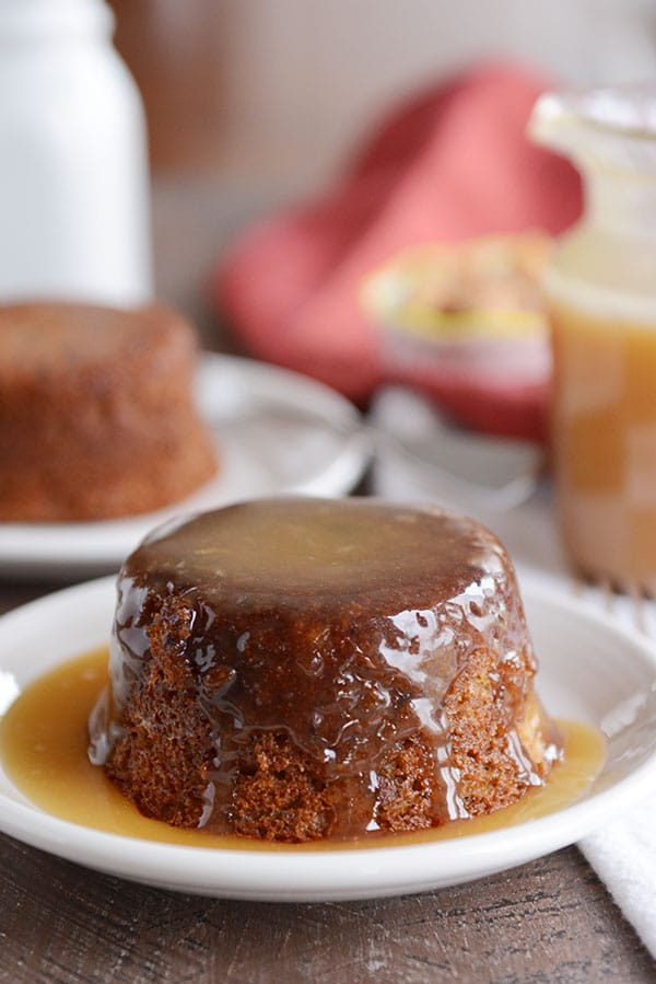 A small, brown cake covered in a light brown sticky toffee sauce.