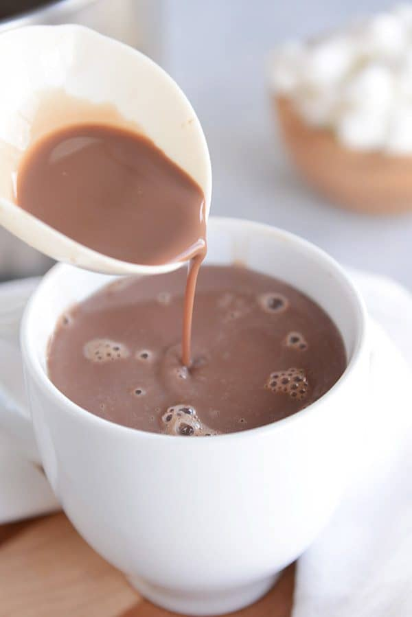 A ladle of hot chocolate being poured in a white mug.