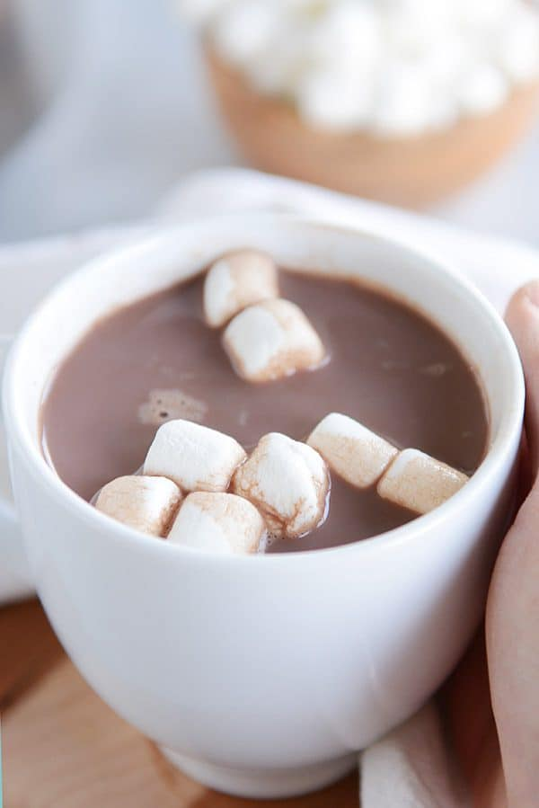A white mug of steaming hot chocolate and marshmallows floating on the top.
