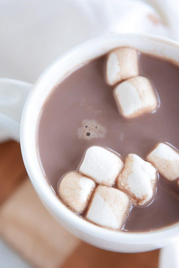 A top-view of a white mug of steaming hot chocolate and marshmallows floating on the top.