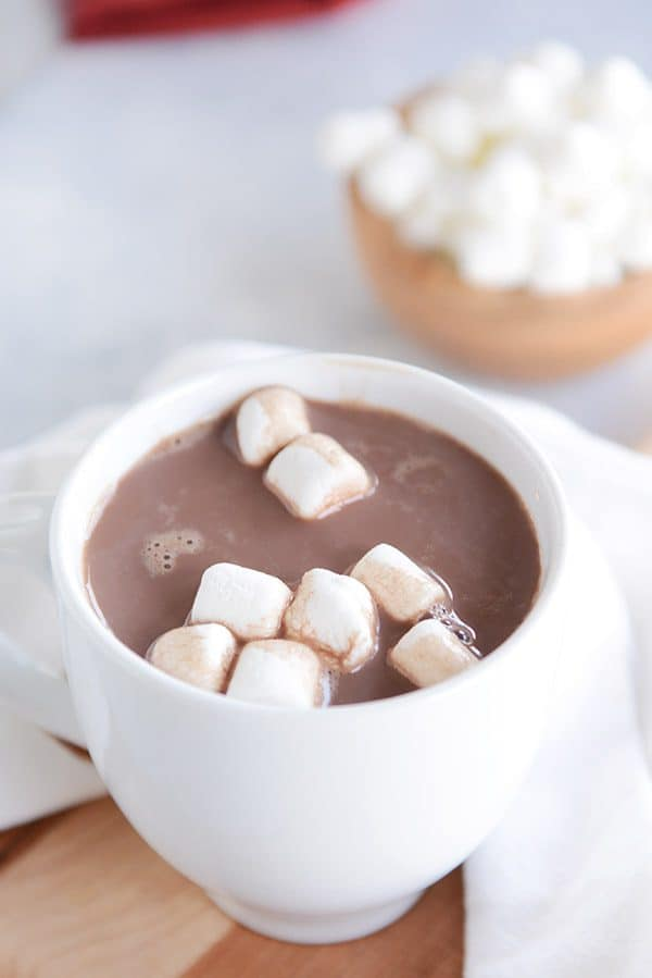 A white mug of steaming hot chocolate and marshmallows floating on the top with a bowl of marshmallows in the background.