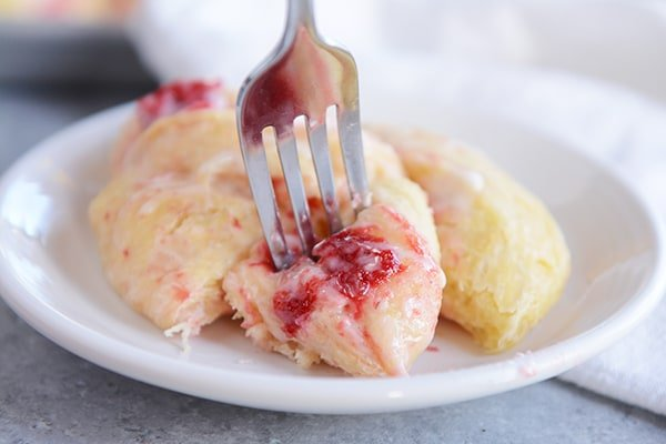 A strawberry cream cheese roll on a plate with one bite cut out on a fork ready to eat.