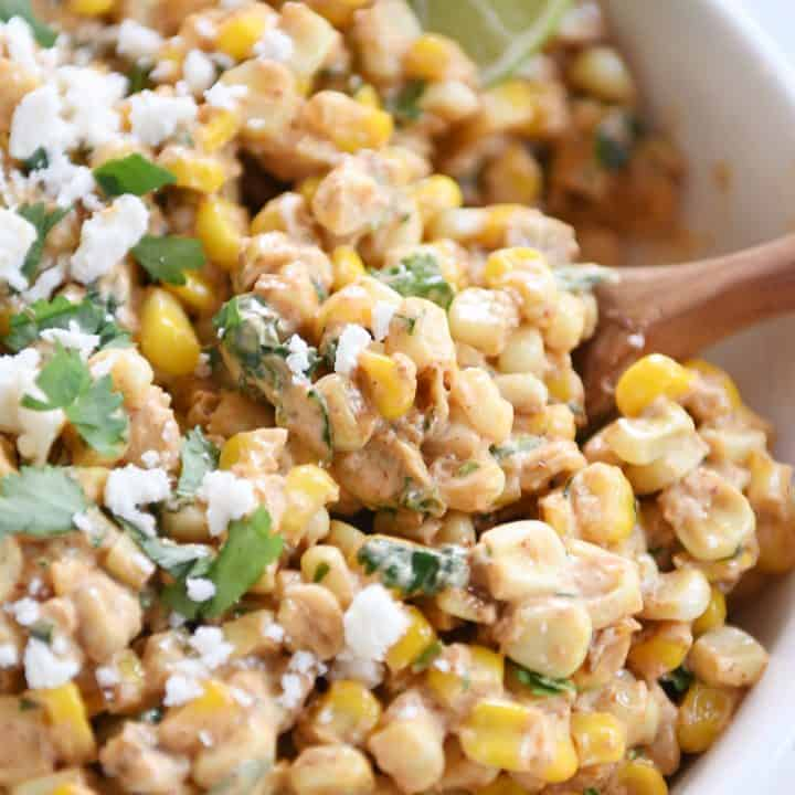 Mexican street corn salad, chopped cilantro, lime with wooden spoon.