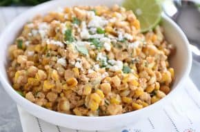 White bowl filled with Mexican street corn salad, topped with cilantro and lime.