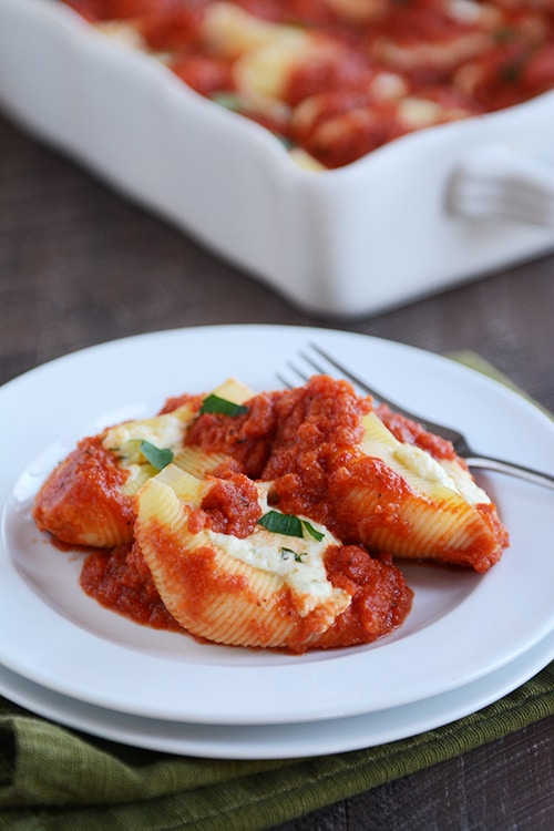 Three ricotta cheese-stuffed pasta shells topped with red sauce, on a white plate.