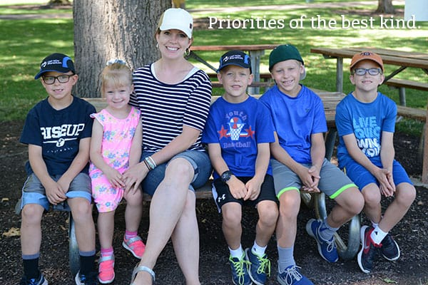 A mother and five kids sitting on a picnic bench.