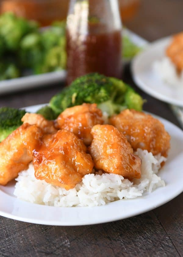 Baked sweet and sour chicken pieces over white rice with steamed broccoli.