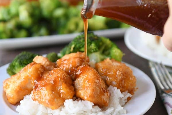 Baked sweet and sour chicken over rice on white plate being drizzled with sweet and sour sauce.