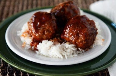 sweet and sour meatballs over white rice on a white plate