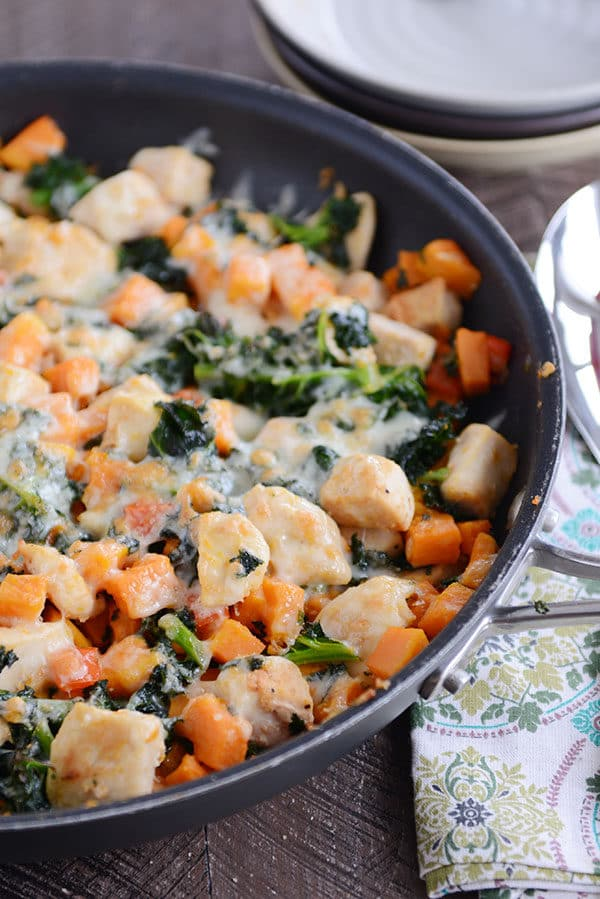 A skillet filled with cubed sweet potato, kale, cooked chicken, and melted cheese.