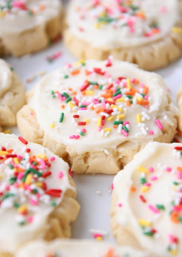 Lots of frosted Swig sugar cookies with sprinkles on white tray.