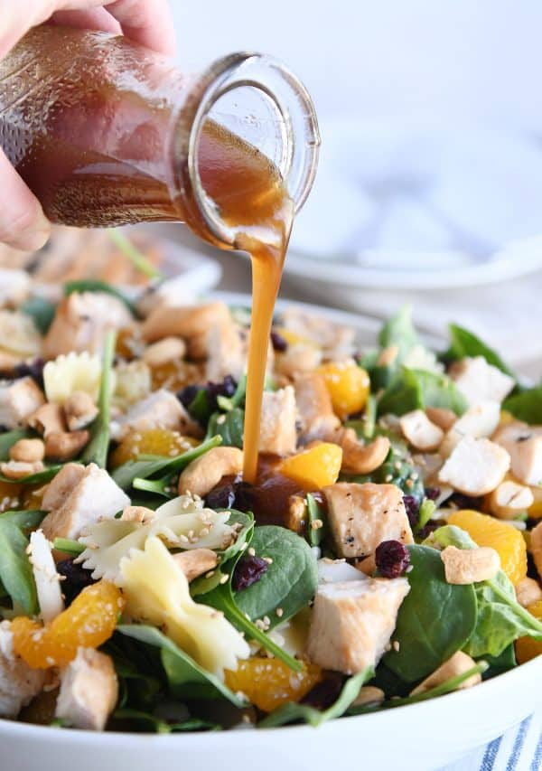 Pouring teriyaki dressing over bowtie pasta salad.