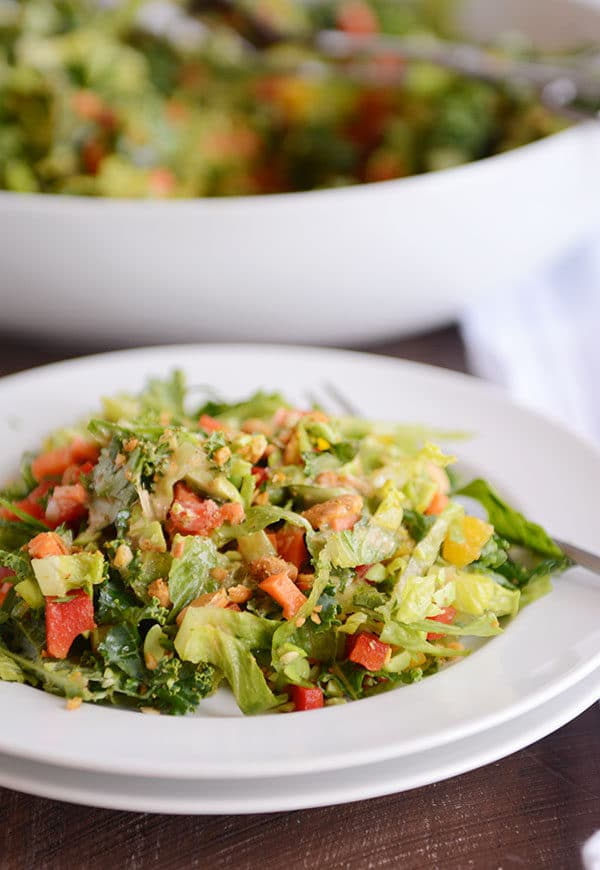 A white plate of chopped Thai salad with the bowl of the rest of the salad behind it.