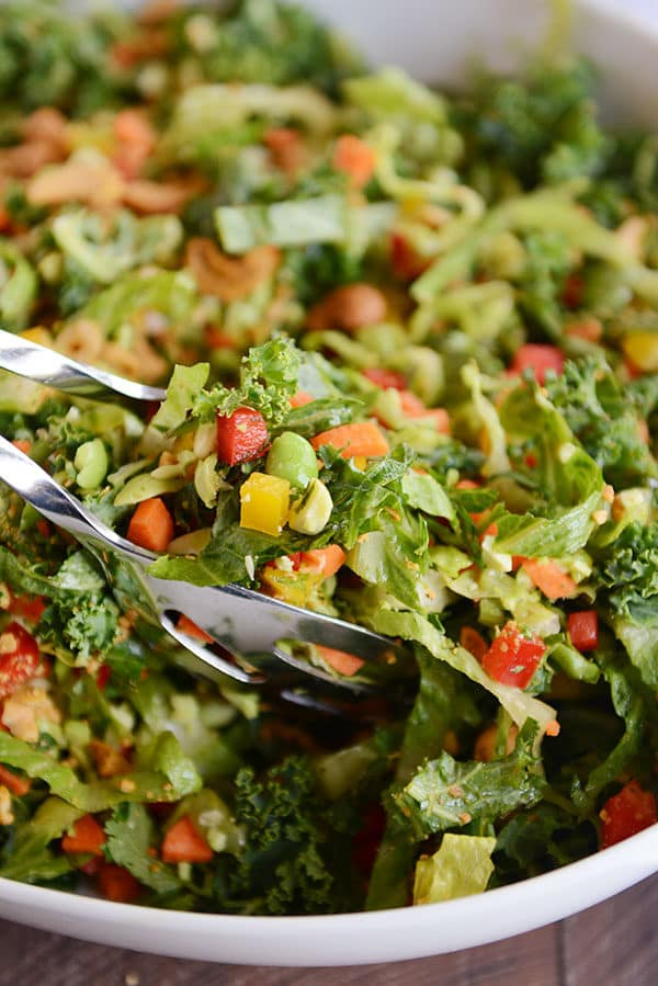 Metal tongs taking a large scoop of chopped Thai salad out of a white bowl.