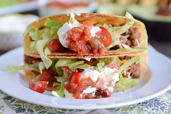 Two hard-shelled tacos stacked on top of each other, filled with ground beef, lettuce, tomatoes, and sour cream.