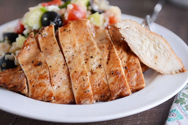 A grilled chicken breast cut up in thick slices next to a quinoa, olive, and tomato salad.