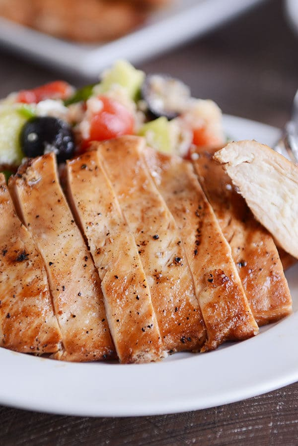 A grilled chicken breast cut in slices next to a quinoa, olive, and tomato salad.
