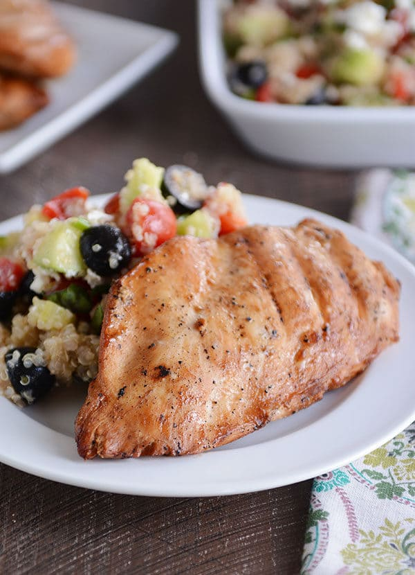 A grilled chicken breast and quinoa vegetable salad on a white plate.